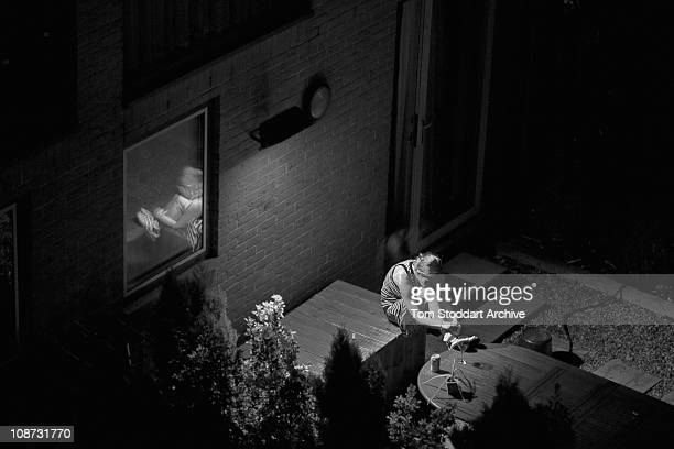 A woman is unknowingly photographed late at night in her garden as she sits alone deep in thought