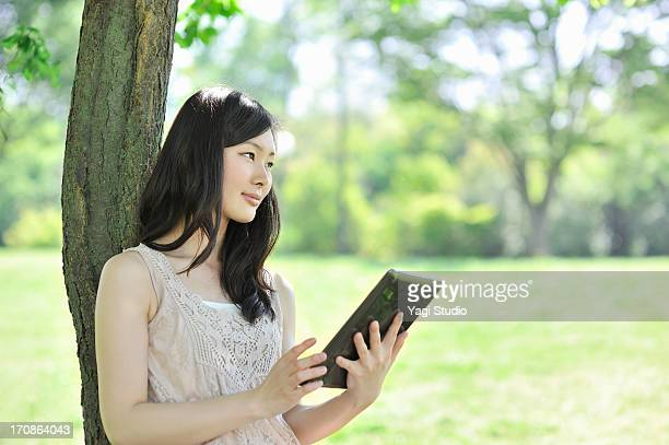 Woman is using a digital tablet leaning on tree in