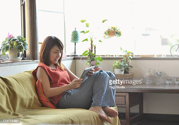 Woman is using a digital tablet on the sofa