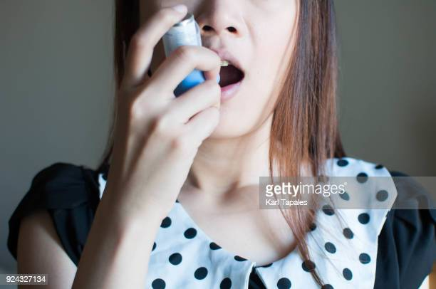 a woman is using an asthma inhaler - asthmatic stock photos and pictures