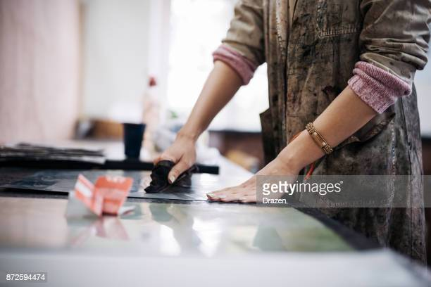 woman is using dark ink colors for her next intaglio prints - intaglio stock pictures, royalty-free photos & images