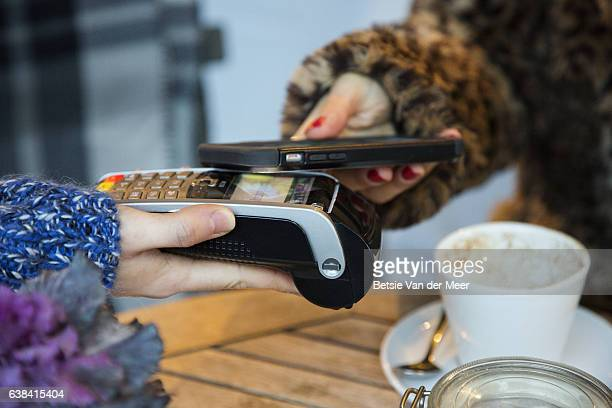 Woman is using her mobilephone for contactless payment with creditcard reader.