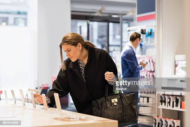 woman is using smart phone at table in showroom - electronics store stock photos and pictures