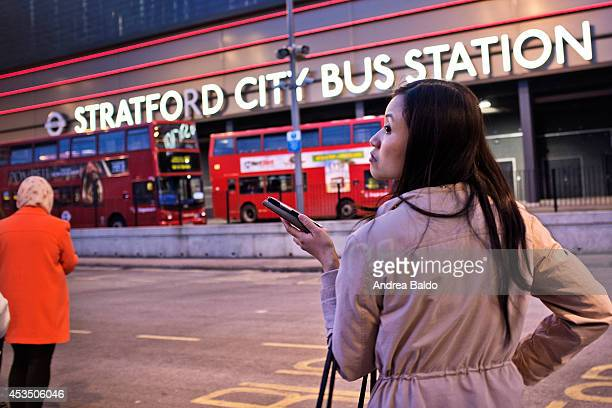 A woman is waiting for a bus at the Stratford City Bus Station in Stratford East London