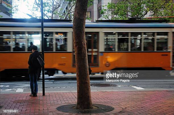 Woman is waiting for the bus on a bus stop on Market Street in downtown San Francisco, California, USA. The woman is wearing a black coat with black...