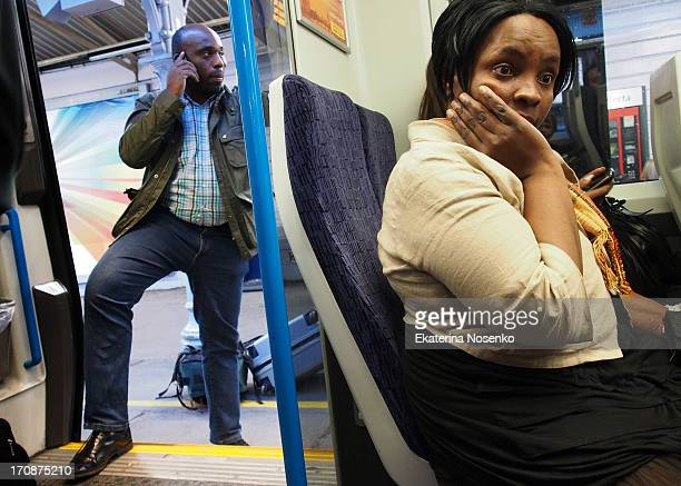 Woman is waiting for the train to start moving while a man is still boarding talking on his mobile phone. Commuter's train, London, the UK.