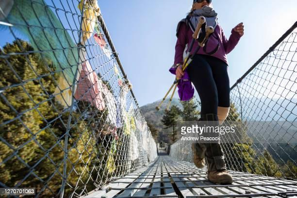 a woman is walking across a suspension bridge, sagarmatha national park, khumbu region, nepal. - suspension bridge stock pictures, royalty-free photos & images