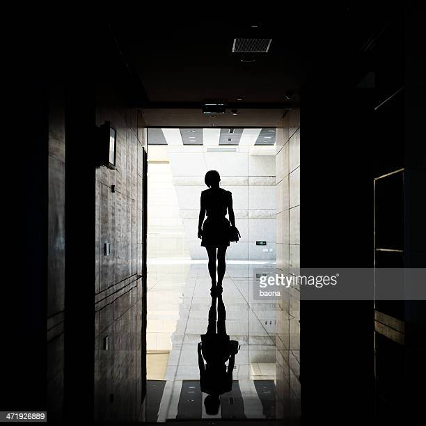 A woman is walking down a corridor into the light