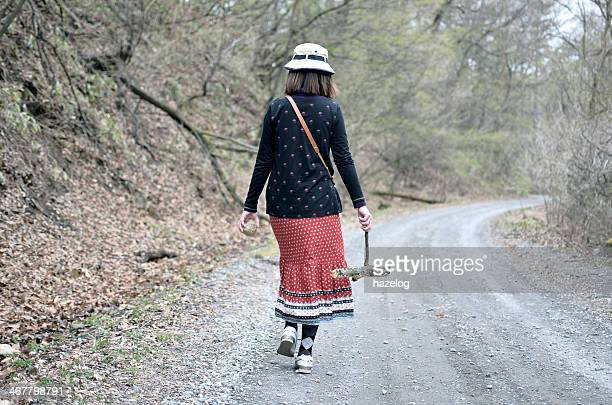 Woman is walking in the mountain gravel path