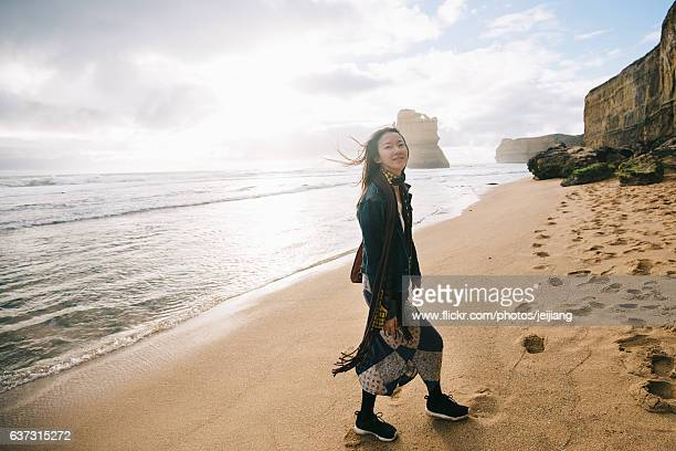 A Woman is walking on beach while looking to camera with smile