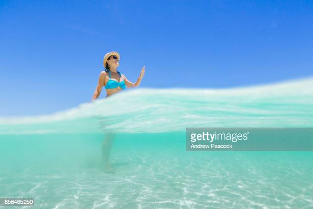 A woman is walking on sand through a clear blue ocean.