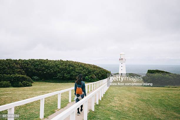 A Woman is walking to a lighthouse