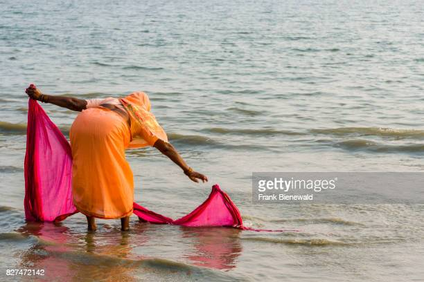 A woman is washing her sari on the beach of Ganga Sagar celebrating Maghi Purnima festival
