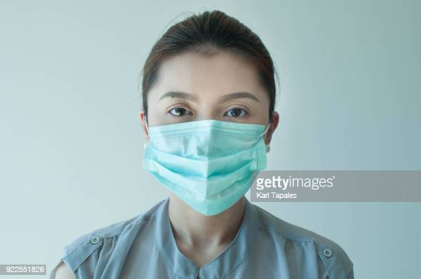 a woman is wearing a green surgical mask - virus photos et images de collection