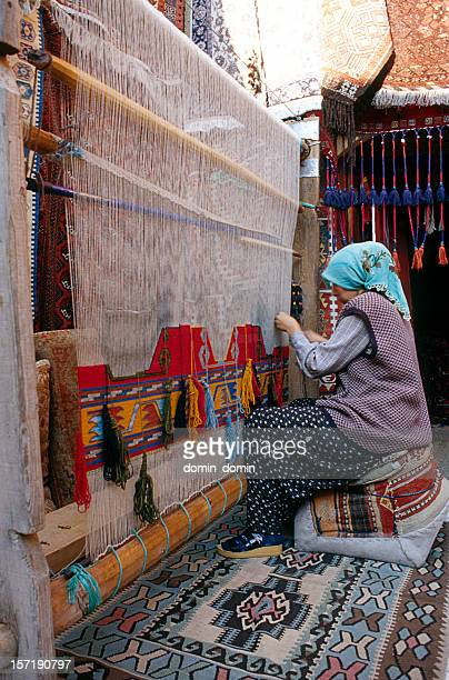 woman is weaving traditional turkish carpet in her house - woven stock photos and pictures
