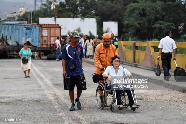 A woman is wheeled across the Simon Bolivar International Bridge from San Antonio del Tachira Venezuela to Cucuta Colombia on March 11 after...