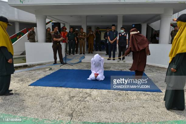 A woman is whipped by a member of the sharia police in public in Banda Aceh on December 10 after she was caught in close proximity with a man who is...