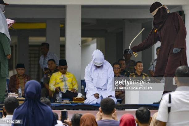 Woman is whipped in public by a member of the Sharia police in Banda Aceh on September 19, 2019. - A trio of canoodling couples were publicly flogged...