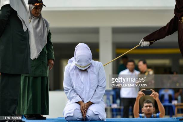 A woman is whipped in public by a member of the Sharia police in Banda Aceh on October 31 after being caught having an affair with Aceh Ulema Council...