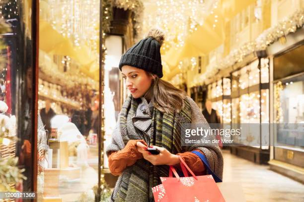 woman is window shopping in decorated street. - merchandise stock pictures, royalty-free photos & images