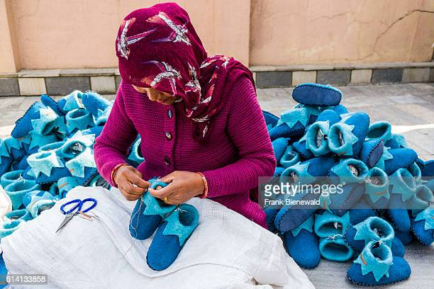 A woman is working at felt shoes