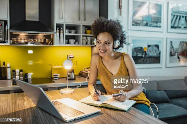 a woman is working from home on a laptop in the kitchen - makeshift stock pictures, royalty-free photos & images