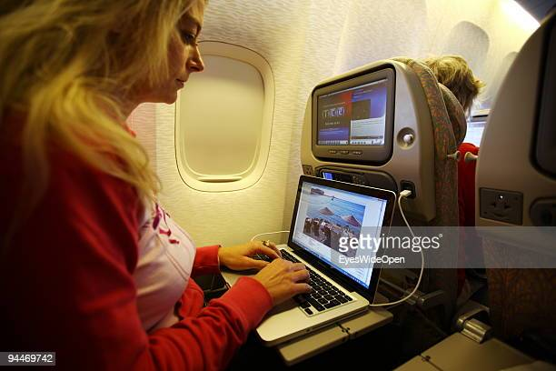A woman is working with a notebook and listen to music with headphones on board of a Emirates Airline passenger jet on December 08 2009 in Trivandrum...
