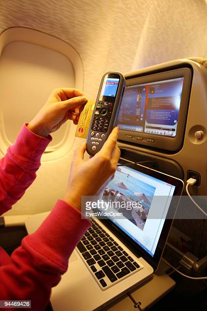 A woman is working with a notebook and makes a telephone call paid by credit card on board of a Emirates Airline passenger jet on December 08 2009 in...