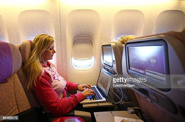 A woman is working with a notebook on board of a Emirates Airline passenger jet on December 08 2009 in Trivandrum India Since some month its new that...