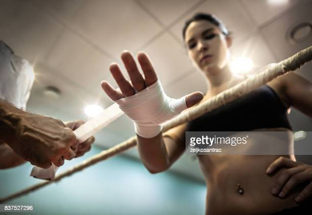 Woman is wrapping hands with pink boxing wraps