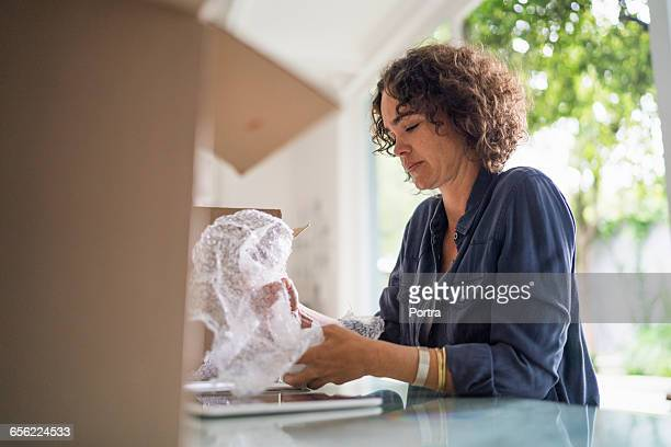 woman is wrapping object while sitting at table - donna bendata foto e immagini stock