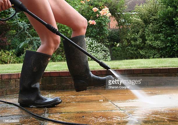 Woman jet washing patio