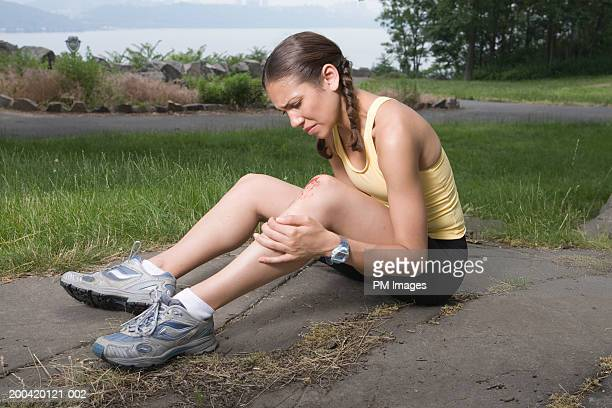 woman jogger holding injured knee - leg wound stock pictures, royalty-free photos & images