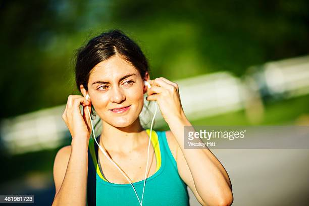 Woman jogger plugging in her ear plugs