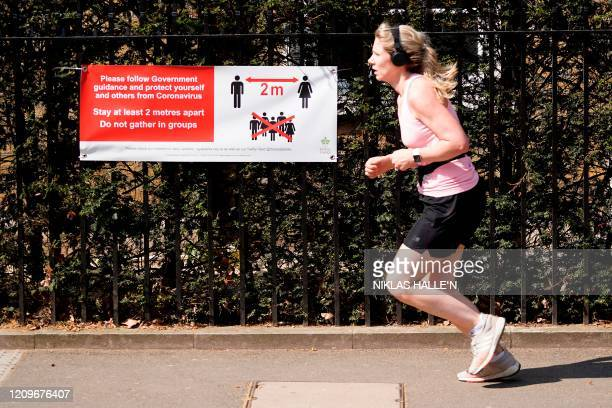 A woman jogger runs past a sign telling people to adhere to social distancing guidelines and stay two meters apart in central London on April 11 as...