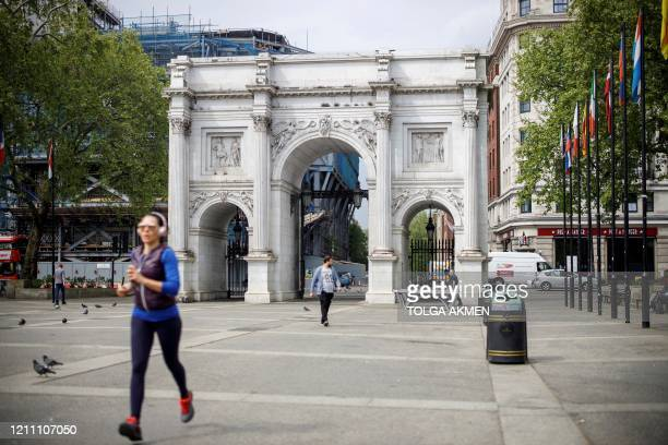 A woman jogger runs past an almost deserted Marble Arch tourism site in London on April 27 as tourists stay away due to the COVID19 pandemic Prime...