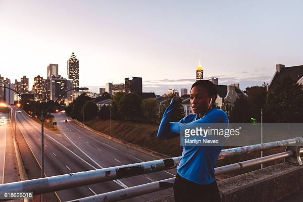 woman jogger stretching with skyline in the background