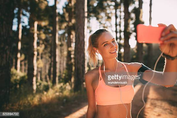 Woman jogger taking a selfie on morning nature trail run