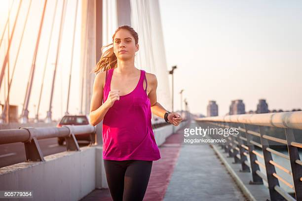 Woman jogging across the bridge