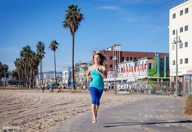 woman jogging at the beach - boardwalk stock pictures, royalty-free photos & images