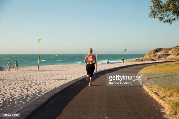 woman jogging by the beach at sun set - perth australia stock pictures, royalty-free photos & images