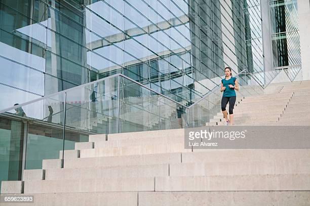 Woman jogging down a staircase