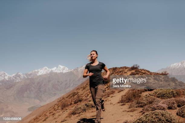 Woman jogging down from peak, Annapurna Circuit, the Himalayas, Muktinath, Nepal
