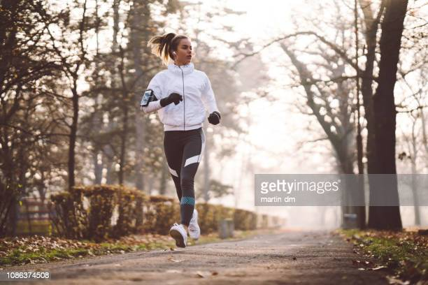 woman jogging during winter morning - jogging stock pictures, royalty-free photos & images