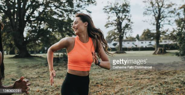 woman jogging in a park - women stock pictures, royalty-free photos & images