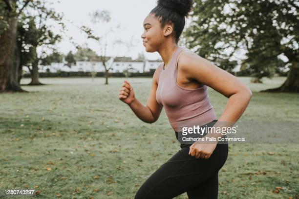 woman jogging in a park - running stock pictures, royalty-free photos & images