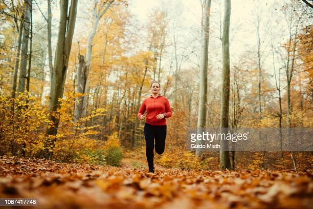Woman jogging in autumnal park.