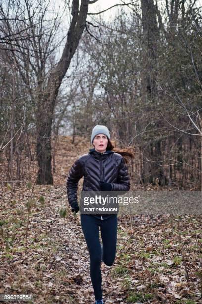 """kvinna jogging i staden offentlig park på vintern. - """"martine doucet"""" or martinedoucet bildbanksfoton och bilder"""