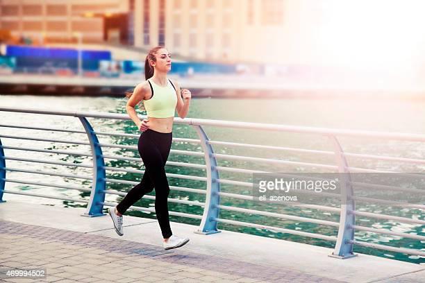 Woman jogging in Dubai Marina.