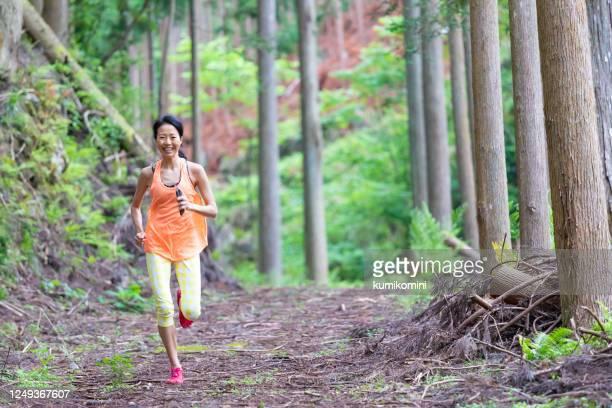 woman jogging in mountain - active lifestyle stock pictures, royalty-free photos & images